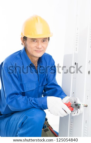 Vertical shot of a professional electrician doing maintenance work