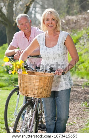 Vertical shot of a senior couple with their bicycles on a sunny day smile at the camera with the woman in front carrying spring flowers in her basket.