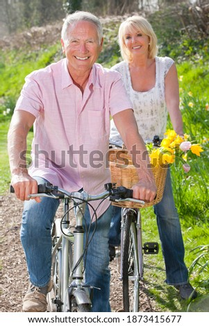 Vertical shot of a senior couple with their bicycles on a sunny day smile at the camera with the man in front.