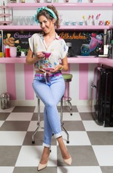 Vertical shot of a woman in retro clothing sitting on a chair at an old-fashioned diner.