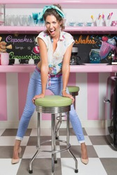 Vertical shot of a woman in retro clothing standing against a chair at an old-fashioned diner.