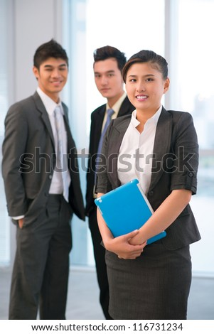 Vertical shot of a young businesswoman posing for the camera, her male colleagues standing in the background