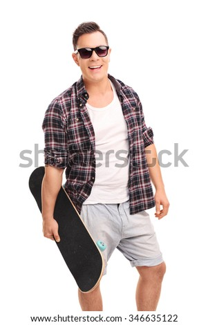 Vertical shot of a young confident man holding a skateboard and looking at the camera isolated on white background #346635122