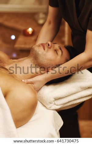 Vertical shot of a young handsome man enjoying professional full body massage lying with his eyes closed relaxing happiness wellness wellbeing relaxation pampering resort hotel service masseuse #641730475