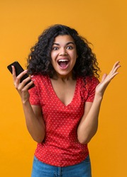Vertical shot of amazed girl with mobile phone in hands celebrating victory, hitting jackpot in lottery, making bets online at bookmaker's website. Female blogger happy to get one mil
