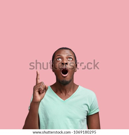 Vertical shot of amazed young African American male with widely opened mouth, has unexpected expression, dressed in casual t shirt, isolated over pink background. People and advertisment concept #1069180295