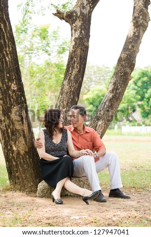 Vertical shot of an elderly couple embracing under the tree