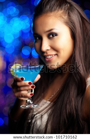 Vertical shot of an elegant young woman holding a cocktail