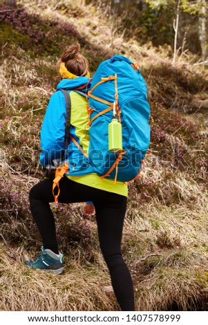 Vertical shot of backpacker overcomes hill by foot, carries touristic rucksack, puts all efforts, demonstrates endurance, enjoys extreme activities while traveling, climbes up. Trekking and hiking