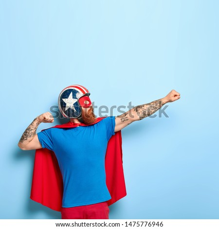 Vertical shot of bearded man makes flying gesture, clenches fists, has goal to achieve, wears protective headgear, red cape, pretends being heroic character, has superhuman power isolated on blue wall
