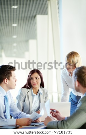 Vertical shot of business people gathered for a meeting - stock photo