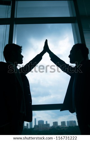 Vertical shot of business people giving a high five, only silhouettes can be seen