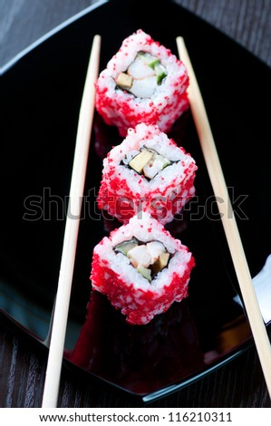 Vertical shot of California sushi rolls and chopsticks on a black plate