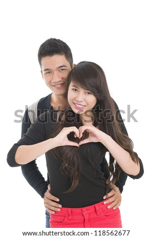 Vertical shot of cheerful young people expressing their love by forming a heart shape
