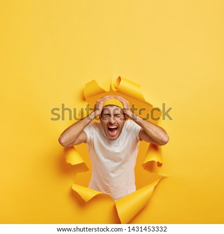 Vertical shot of emotional guy touches head with both hands, wears casual white t shirt, stylish yellow hat, poses in ripped hole paper, shouts from negative emotions, feels annoyed. Bad feelings #1431453332