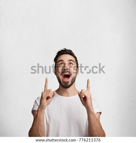 Vertical shot of excited surprised male has beard and mustache indicates with fore fingers upwards, advertises something amazing, stands against white concrere wall with copy space for promotion