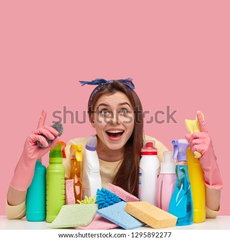 Vertical shot of good looking dark haired young woman with pleased expression, points at ceiling, wears headband, wears rubber protective gloves, ready for washing in house, uses cleaning agents #1295892277
