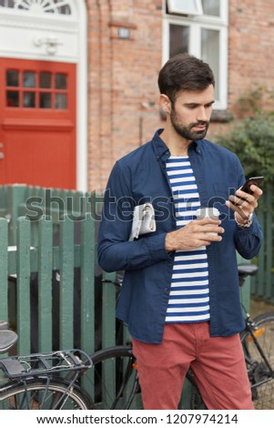 Vertical shot of handsome young man with dark bristle, updates app in social networks, holds modern smart phone, carries newspaper under arm, drinks takeaway coffee, stands in rural territory #1207974214