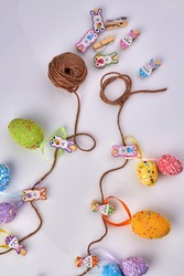 Vertical shot of motley easter eggs with thread.