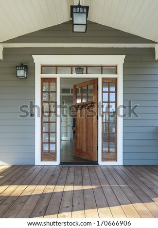 Vertical shot of wooden front door  of an upscale home with windows/Exterior shot of a Wooden Front Door