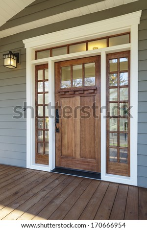 Vertical shot of wooden front door  of an upscale home with windows/Exterior shot of a Wooden Front Door