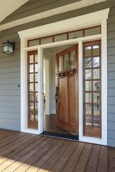 Vertical shot of wooden front door  of an upscale home with windows/Exterior shot of an open Wooden Front Door
