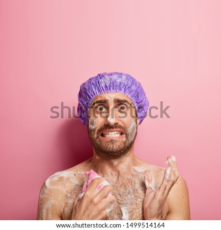Vertical shot of worried man being in hurry during morning, washes body with gel and sponge, wears waterproof headgear, stands naked in bathroom, takes shower, isolated over pink studio wall