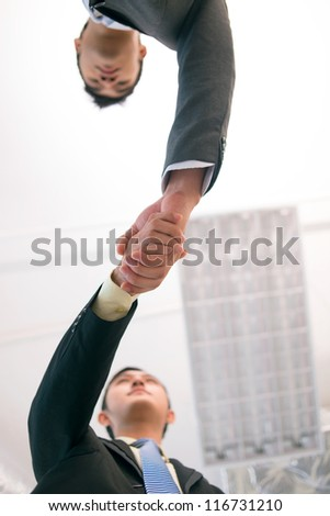 Vertical shot of young business people shaking hands to conclude the deal