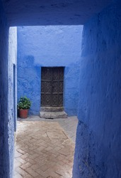 Vertical shot with ancient black door with flower pot and beautiful blue wall in Arequipa, Peru