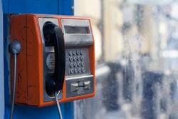 Vertical side view of damaged orange public phone with near a dirty window with selective focus