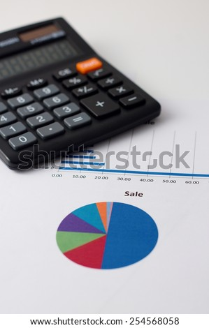 Vertical simple photo with color pie chart printed on paper sheet as main motif and with black calculator in background