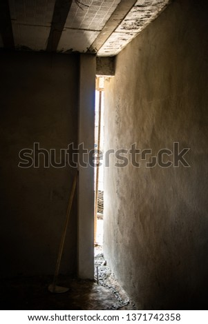 vertical slit on a wall in a construction with some light coming in from the outside #1371742358
