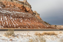 Vertical snow streaks on side of red rock mountain along empty highway in rural New Mexico