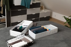 Vertical storage of clothing. Sorted clothes in baskets and shelves in a modern bedromm. Cleaning concept.