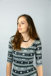 vertical studio portrait of young beautiful woman with long brown hair looking far to the side wearing white and grey patterned short sleeve dress and brown neckless