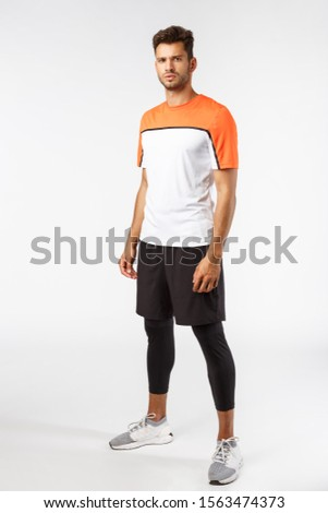 Vertical studio shot male football player in activewear, sneakers standing determined, ready score goal, squinting frowning self-assured, prepare for workout, endurance and sport concept