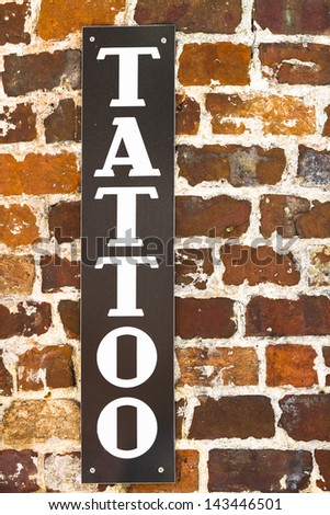 Vertical tattoo sign on a brick wall