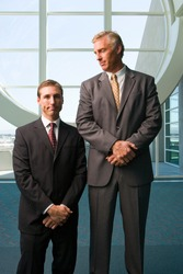 Vertical three quarter front view of two businessmen standing besides each other with the taller one looking at the shorter in office lobby.