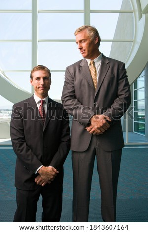 Vertical three quarter front view of two businessmen standing besides each other with the taller one looking at the shorter in office lobby. Foto stock ©
