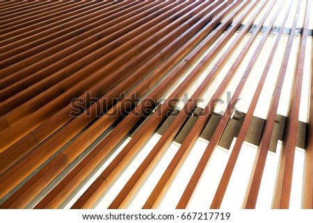 Vertical timber battens on stainless steel frame and stanchions. Wood background.