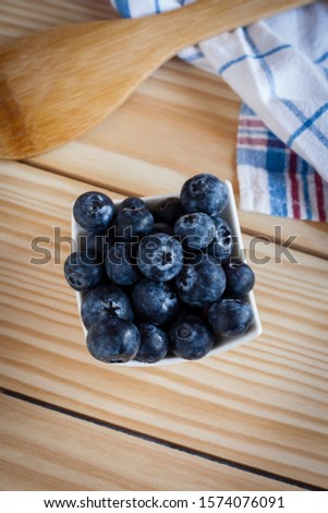Vertical top view food ingredient still life shot of small bowl full of blueberries on a wooden background with spoon and kitchen towel. Fruit ingredients for confectionery with negative space.