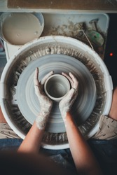 Vertical top view image of female pottery artist working on pottery wheel makes beautiful mug or vase in her own clay studio, Creative People Art and Handcrafted Product
