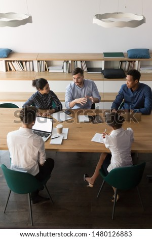 Vertical top view multi-ethnic businesspeople sitting at desk gathered in modern board room discussing planning solve common problems. Concept of teamwork, partnership and brainstorm image from above