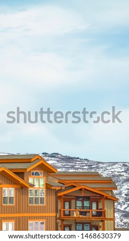 Vertical vertical, tall, magazine, Upper exterior of houses against snow covered mountain and cloudy sky in winter