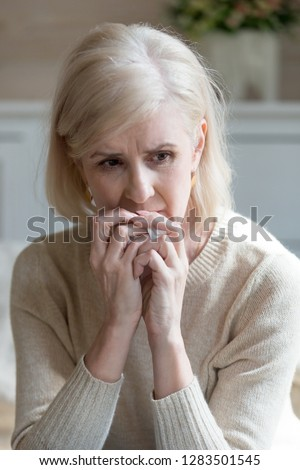 Vertical view image of blond caucasian upset middle aged sixty years woman holding handkerchief in hand sitting alone at home feels unhappy unwell miserable and anguishes mature woman mourns spouse