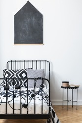 Vertical view of blackboard on the wall of teenagers bedroom with black and white patterned bedding on single metal bed, real photo with mockup