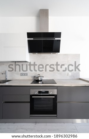 Vertical view of built in appliances, sink, oven, cooker hood, electric stove. Modern kitchen with white cupboards, marble countertop, saucepan on induction glass ceramic surface. Cooking food concept