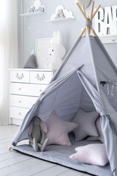 Vertical view of childrens play room with comfort, soft pillows in tent, white wooden dresser, rabbit toy and house decor in bedroom with scandi interior style