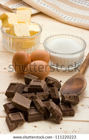 "Vertical view of chocolate ""Cake Ingredients"" on pine wood table."