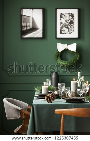 Vertical view of elegant dining room interior with christmas wreath with white bow and posters in black frame on empty green wall and dining table set for christmas dinner, real photo